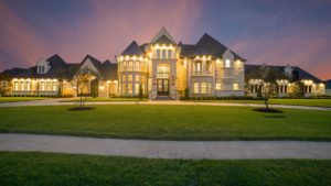 Large mansion with many windows lit up at night