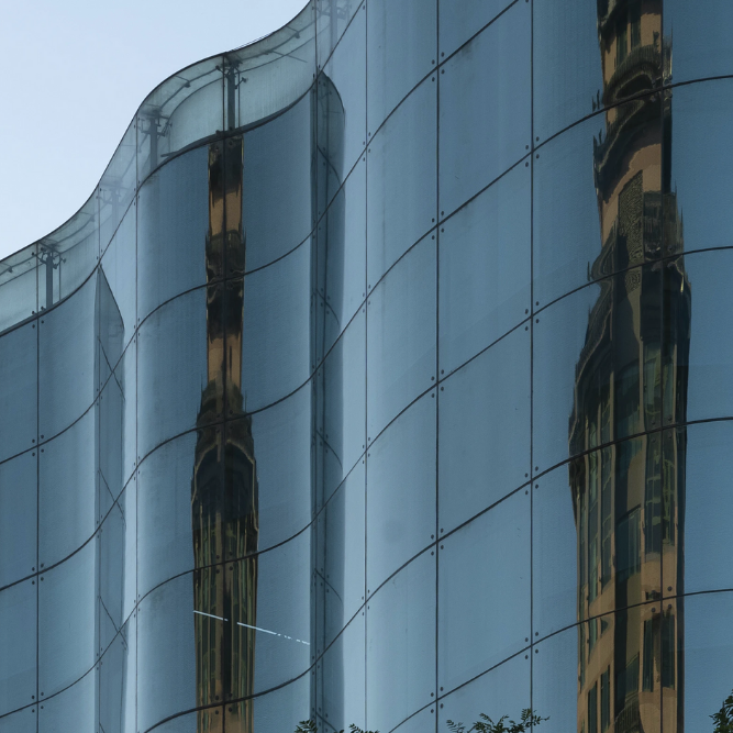 City buildings reflected in a skyrise in the city