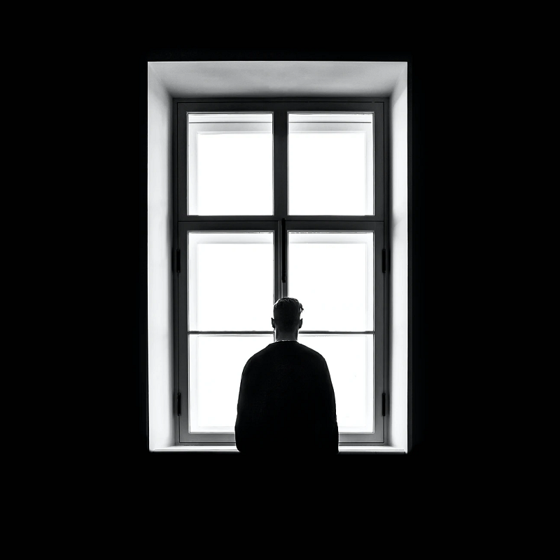 silhouette of a man standing in front of a bright window in a dark room