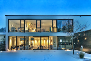 modern home with floor to ceiling windows on every floor creating a wall of windows