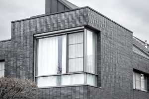 grey modern home with architectural windows around the sides